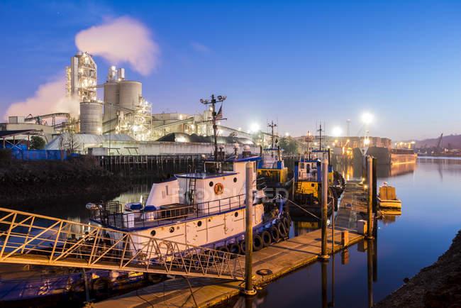 Vista de ángulo alto del remolcador atracado en el puerto con enorme edificio de la fábrica, Seattle, Washington, EE.UU. - foto de stock