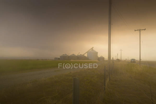 Dust storm over rural landscape with grain silos in distance — Stock Photo