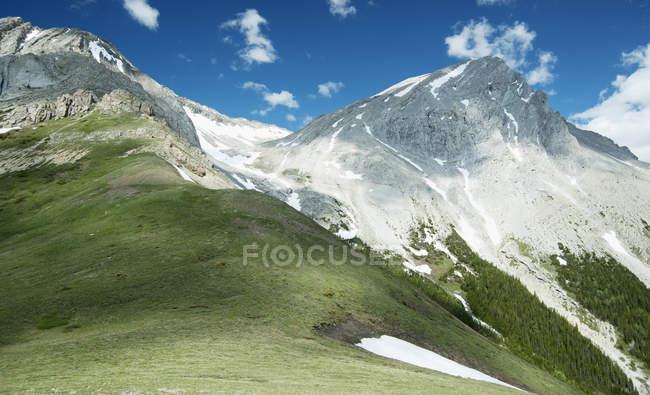 Горные вершины со снегом и травой под голубым небом, Кананаскис, Калгари, Альберта, Канада — стоковое фото