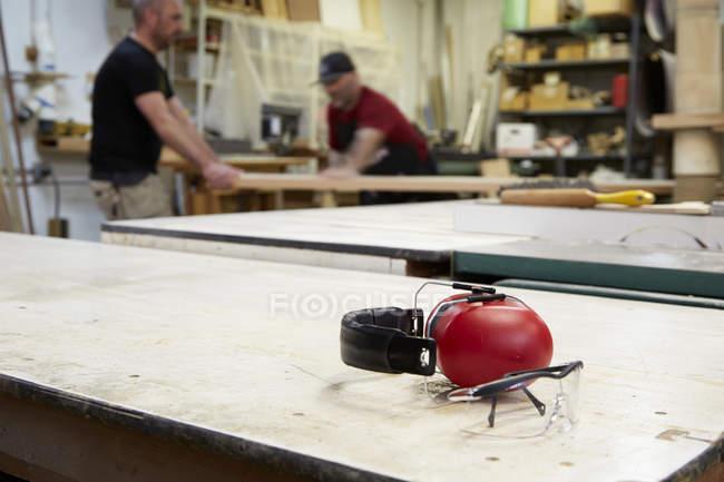 Primer plano de auriculares y gafas de seguridad en la mesa del taller - foto de stock