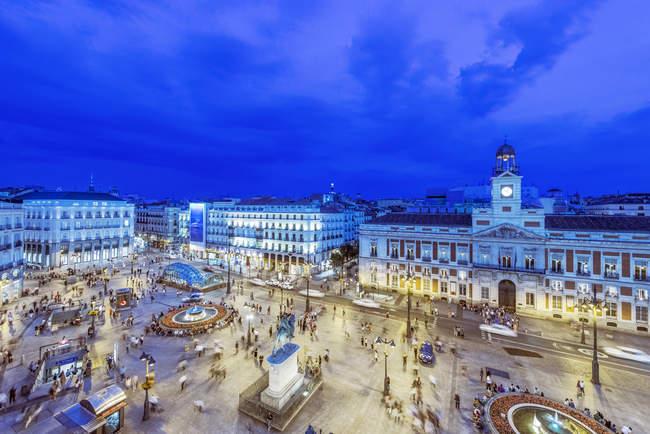 Edificios ornamentados iluminados por la noche en la plaza con multitud de gente, Madrid, Madrid, España - foto de stock