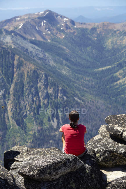 Hiker sitting on rocky hilltop, Washington, USA — Stock Photo