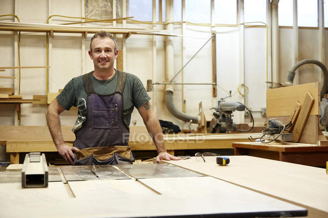 Male carpenter standing and smiling in workshop interior — Stock Photo