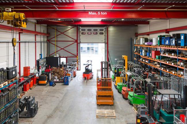 Размытое представление о работнике с использованием техники в интерьере склада — стоковое фото