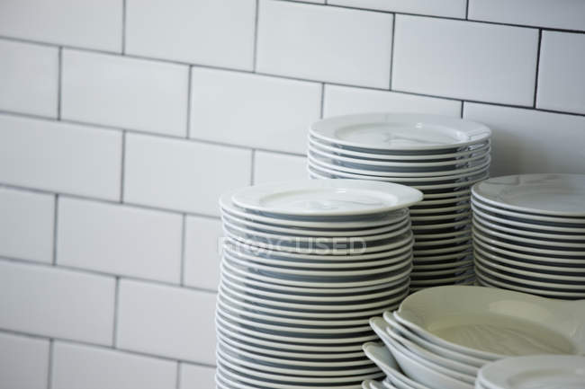 Close-up of stacked plates in restaurant kitchen with white tiles — Stock Photo