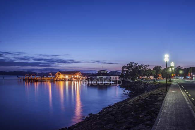 Edificios iluminados en el agua al amanecer - foto de stock