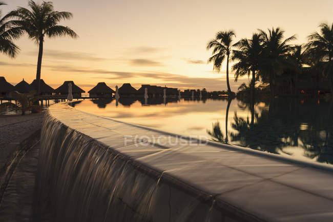Palm trees overlooking tropical resort at sunset, Bora Bora, French Polynesia — Stock Photo