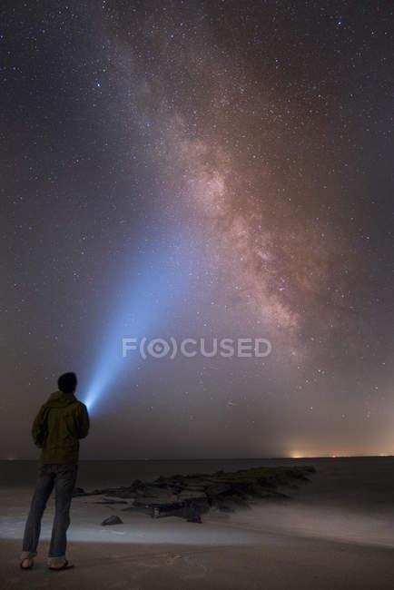 Rear view of man shining flashlight on starry sky, Cape May, New Jersey, USA — Stock Photo