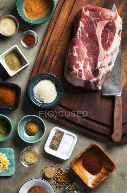 Cutting board with pork shoulder and variety of spices — Stock Photo