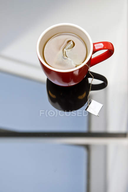 Tea bag steeping in mug on glass table. — Stock Photo
