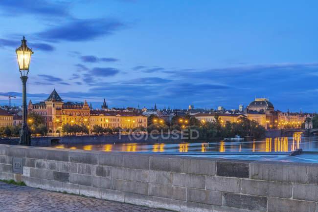 Charles Bridge and city illuminated at dawn, Prague, Czech Republic — Stock Photo