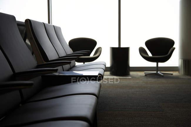 Chaises dans la zone d'attente d'aéroport par la fenêtre — Photo de stock