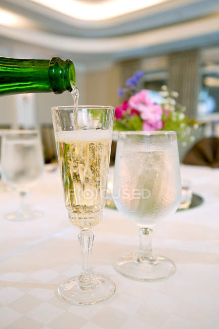 Pouring champagne into drinking glasses on table, close-up — Stock Photo