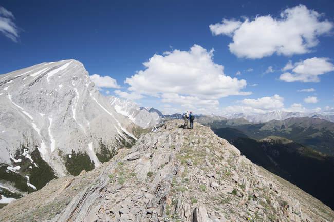 Hikers on mountain peak overlooking remote landscape of Kananaskis, Calgary, Alberta, Canada — Photo de stock