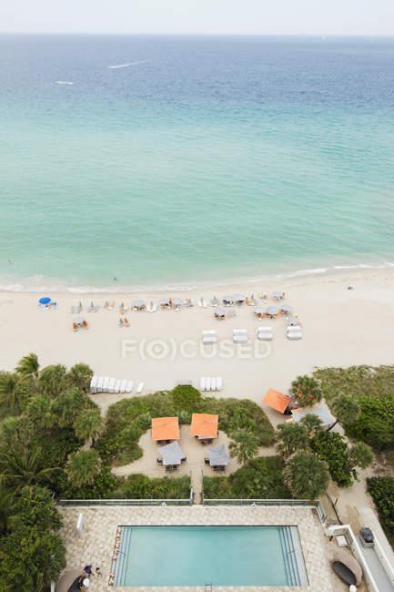 Vista ad alto angolo della piscina dell'hotel e della spiaggia con sedie e turisti — Foto stock