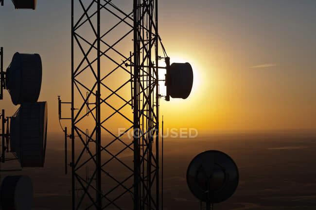 Silhouette de la torre de comunicaciones contra el cielo del sol - foto de stock