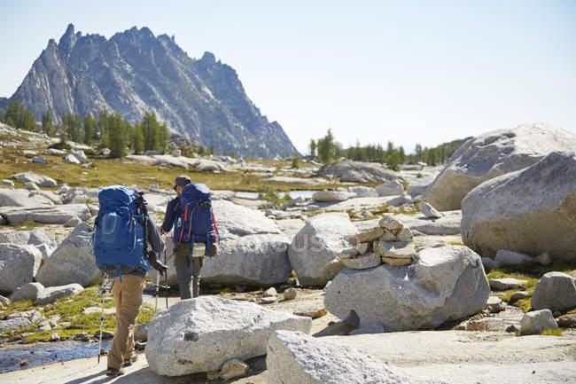 Excursionistas mochileando en el paisaje rural rocoso - foto de stock