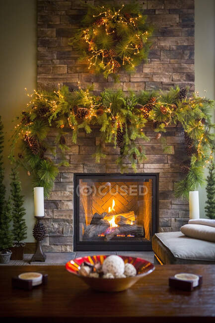 Christmas wreaths over fireplace in living room — Stock Photo