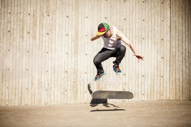 Homme caucasien faisant l'astuce de patin près du mur en bois — Photo de stock