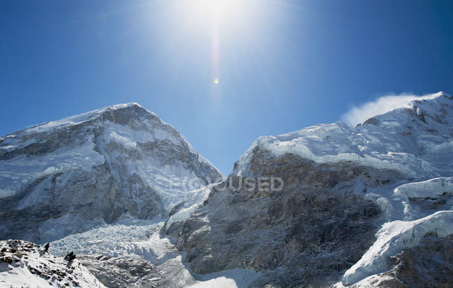 Snow covered mountains and bright sun in blue sky — Stock Photo