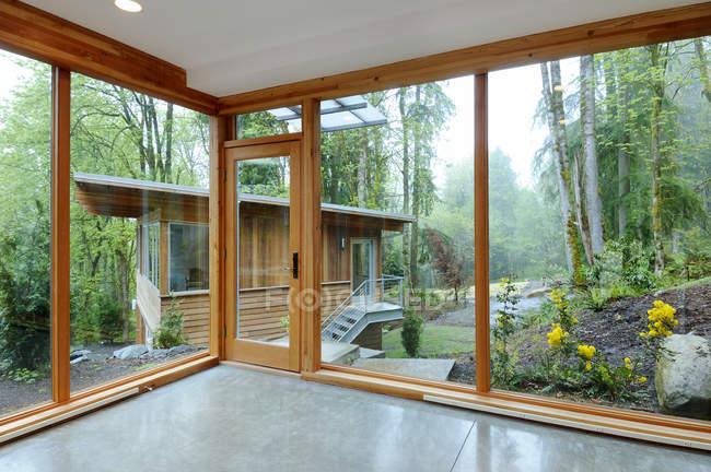 Janelas de vidro da casa moderna na floresta do campo — Fotografia de Stock