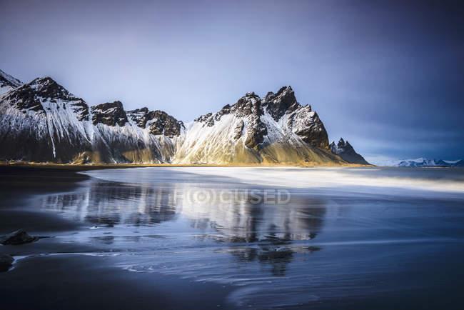 Onde oceaniche sulla spiaggia sotto montagne innevate, Islanda, Europa — Foto stock