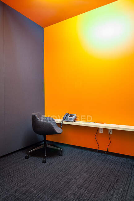 Chair, desk and phone in empty office — Stock Photo