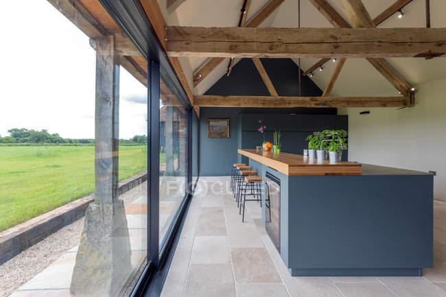 Бар для сніданків і скляна стіна на сучасній кухні — стокове фото