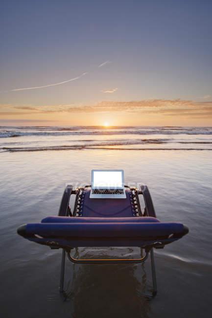 Laptop auf Liegestuhl mit Blick auf Sonnenuntergang am Strand — Stockfoto