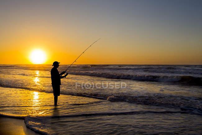 Силует людини риболовля в хвилях на пляжі на заході сонця — стокове фото