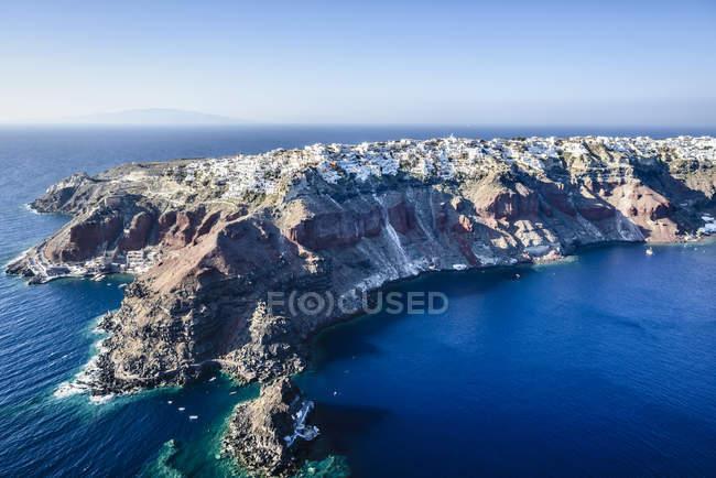 Aerial view of city built on rocky coastline, Oia, Egeo, Greece — Stock Photo
