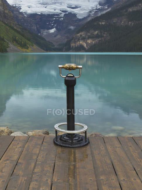 Binoculars overlooking still lake in rural landscape in Banff, Alberta, Canada — Stock Photo