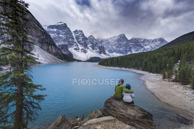 Vista trasera de la pareja sentada en rocas admirando el paisaje del lago de montaña, Parque Nacional Banff, Canadá - foto de stock