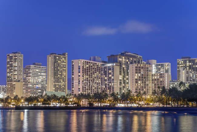 Skyline de la ciudad iluminado en el paseo marítimo, Honolulu, Hawái, Estados Unidos - foto de stock