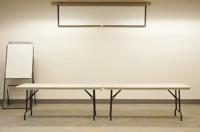 Empty tables under projector screen in classroom — Stock Photo