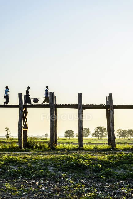 Personnes marchant sur une passerelle en bois surélevée dans le paysage rural du Myanmar — Photo de stock