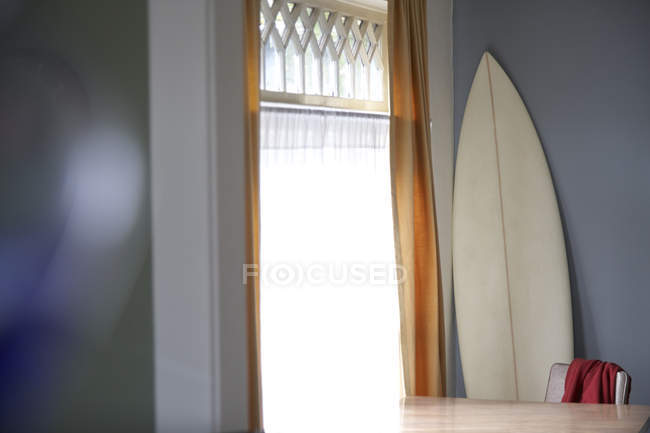Still life of surfboard and table at window indoors in Seattle, USA — Stock Photo