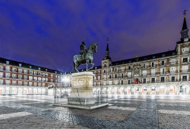 Edificios ornamentados y estatua iluminada por la noche, Madrid, España - foto de stock