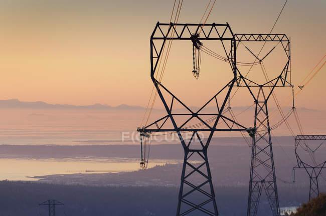 Силуэт линий электропередач и пилона на закате — стоковое фото