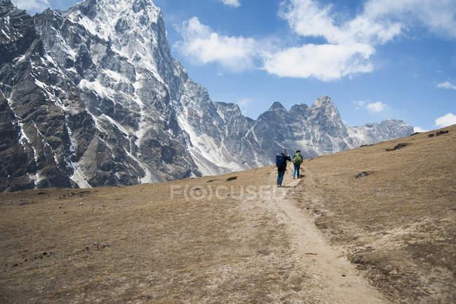 Personas distantes caminando hacia las montañas, Pheriche, región de Khumbu, Nepal, Asia - foto de stock