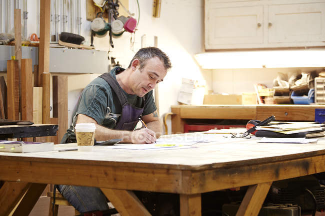 Carpenter sketching at table in workshop interior — Stock Photo