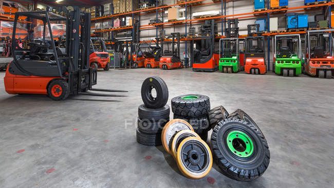 Forklift machinery and tires on floor in warehouse — Stock Photo