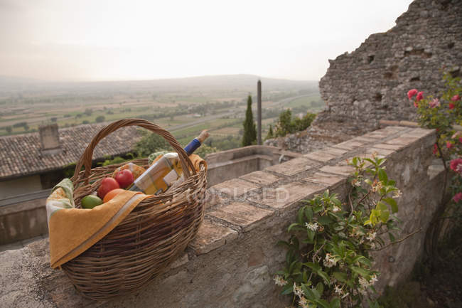 Basket of fresh fruits and wine on stone wall in village — Stock Photo
