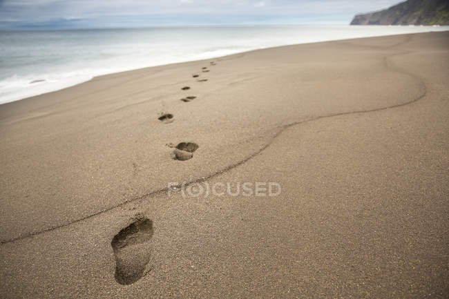 Close-up of footprints in beach sand with sea water — Stock Photo