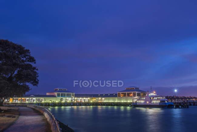 Porto e barco iluminados no crepúsculo, Devonport, Nova Zelândia — Fotografia de Stock