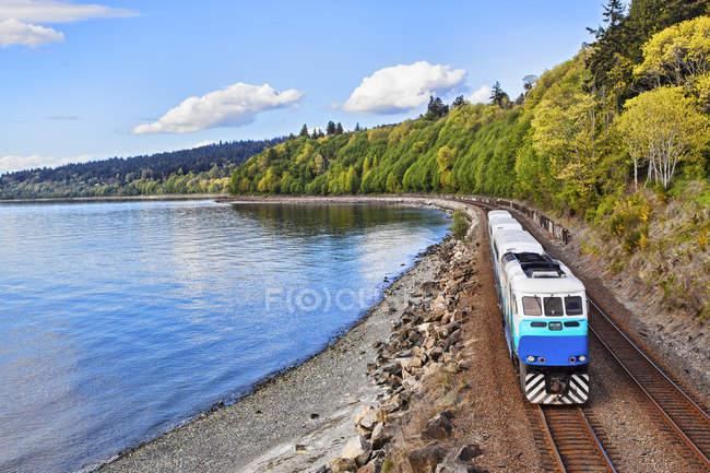 Commuter train on tracks at waterfront, Puget Sound, Washington, EUA — Fotografia de Stock