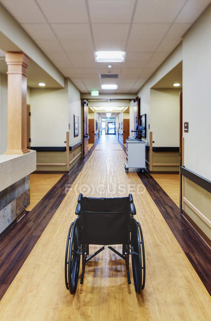 Empty wheelchair in assisted living facility corridor — стокове фото