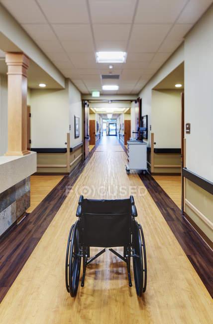 Silla de ruedas vacía en el pasillo de las instalaciones asistenciales - foto de stock