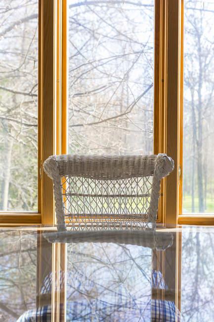 Fenster hinter Korbstuhl und Glastisch — Stockfoto