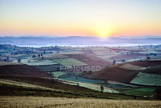 Nascer do sol sobre terras agrícolas na paisagem rural — Fotografia de Stock